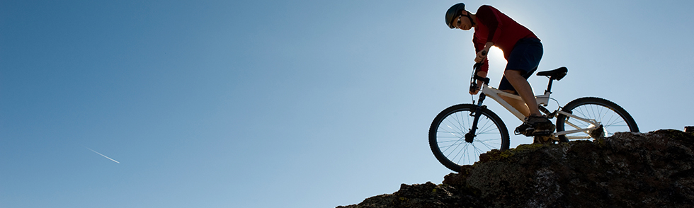 Cyclist on hill silouetted against blue sky