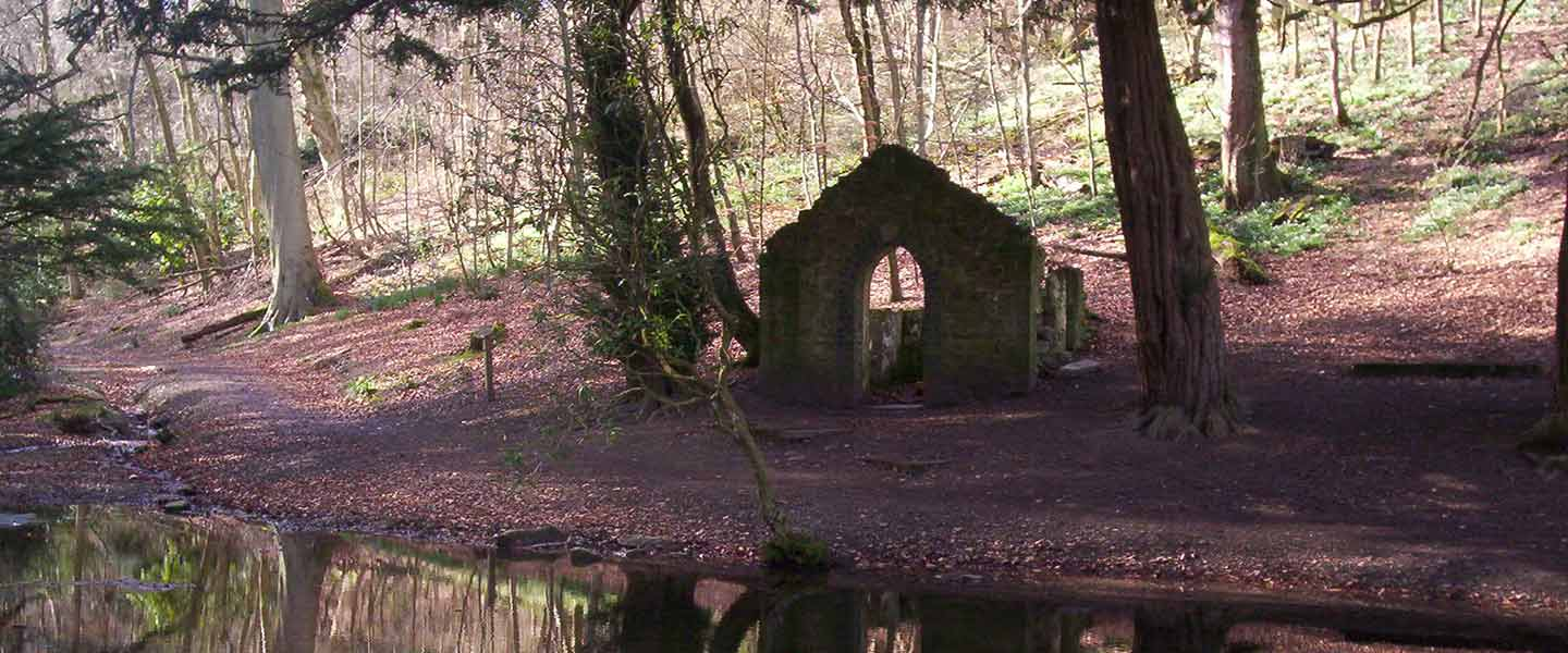 Old stone rectory building in the woods and reflection in the river below